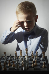 Little boy playing chess.Smart Little genius Child.Chessboard