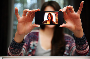 Woman making self photos with smartphone at home