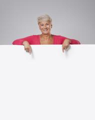 Lovely senior woman showing on empty whiteboard