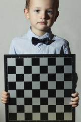 Little boy with chessboard.fashion children.Intelligent game