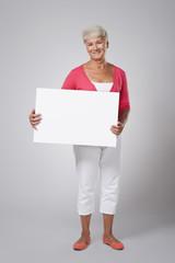 Cheerful senior woman holding blank whiteboard
