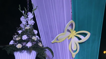 foam butterfly perched on the curtain near the flower arrangemen