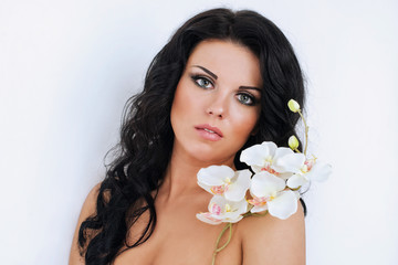 beautiful dark haired girl with orchids on white background