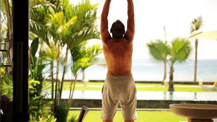 Man stretching on luxury villa patio, view at pool and garden