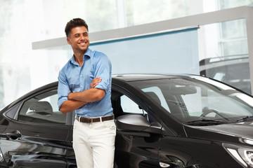 Car Showroom. Happy Man near Car of His Dream.