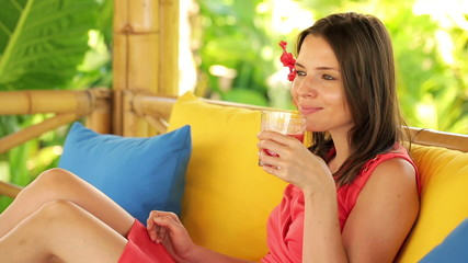 Pretty woman drinking fruit cocktail, relaxing on gazebo bed