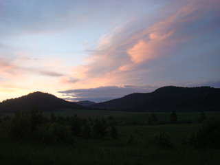 Hills are silhouetted by an blue and pink sky.