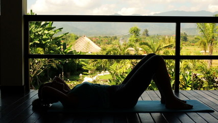 Silhouette of woman doing sit-ups, exercising on terrace