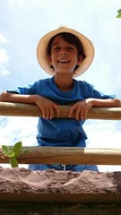 Niño con sombrero en valla
