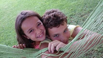 Niño y niña apoyados en hamaca