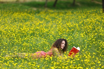 Cute young woman with curly hair lying reading