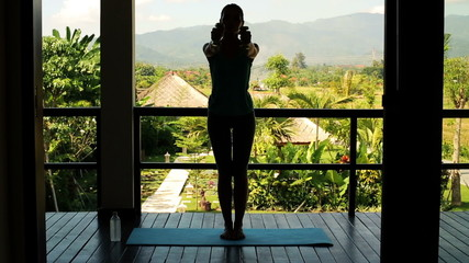 Silhouette of woman exercising with dumbbells on terrace