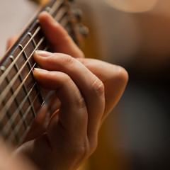 The hand of man playing guitar closeup