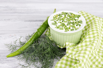 Round plastic bowl of cream with a tuft of dill and pepper near