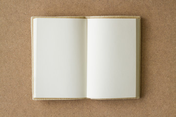 blank book open on a brown textured surface