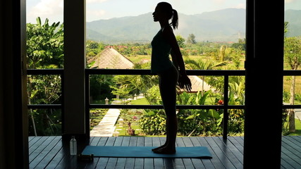 Silhouette of woman exercising, doing squats on terrace