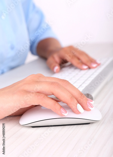 canvas print picture Female hand holding computer mouse, close-up,
