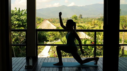 Silhouette of woman exercising on terrace