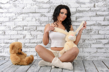 beautiful dark-haired young woman in white with stuffed toys
