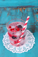 Cold cocktail with forest berries, frozen in ice cubes