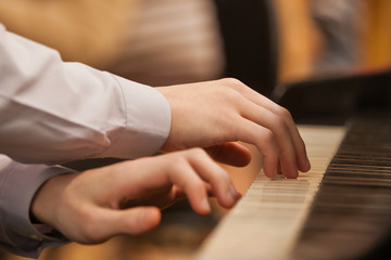 Children's hands on the keyboard of the piano