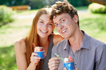 Young couple with a cup of ice cream in summer