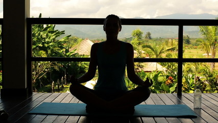 Silhouette of woman meditating on terrace
