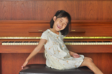 asian child sits in front of the piano