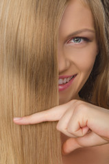 young smilling woman keeps fingers straight hair