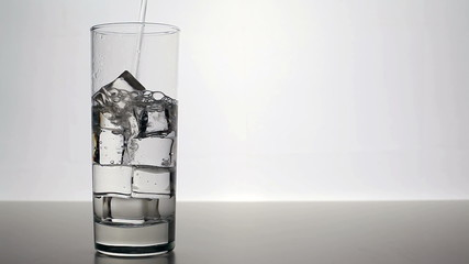 Clean water pours into a glass with ice cubes