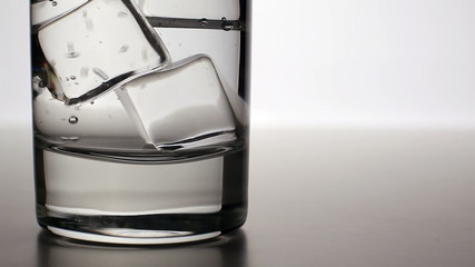 CLOSEUP: Clean water pours into a glass with ice cubes