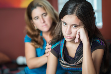 Mother comforts her sad teenage daughter