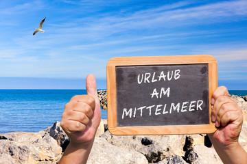 Daumen hoch. Tafel mit Text: Urlaub am Mittelmeer