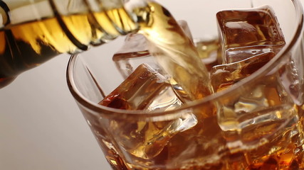 Whiskey pours into a glass with ice cubes