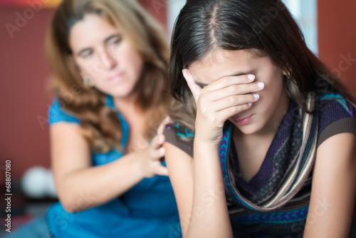 Mother comforts her teen daughter at home