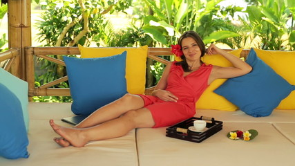 Attractive happy woman lying on gazebo bed in garden