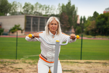 Senior woman in sportwear exercise in outdoor fitness center