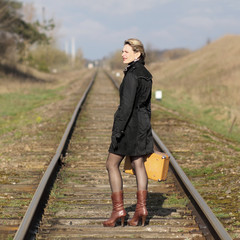 Woman with an old suitcase walking along railway sleepers