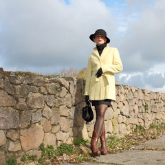 beautiful middle-aged woman in a yellow vintage coat,