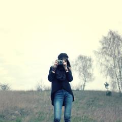 Hipster girl walks  photographs on vintage camera outdoors