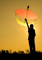 A kid holding a kite in silhouette
