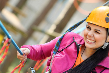 girl in the outfit climbing over obstacles between trees