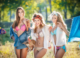 Three sexy women with provocative outfits putting clothes to dry