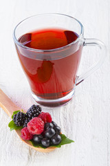Fruit red tea with wild berries in wooden spoon