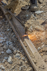 Welder using oxyacetylene cutting torch to cut a a old tram trac