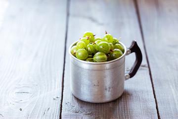 Green gooseberries in a aluminum cup