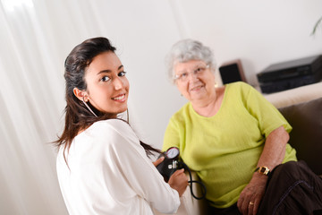 cheerful young doctor taking blood pressure of elderly woman