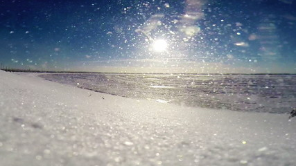 Frozen sea coast:  Snow blizzard during Bright sunny day