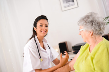 cheerful young nurse giving an injection to elderly woman