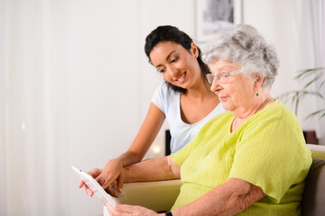 cheerful young girl with elderly woman playing with tablet home